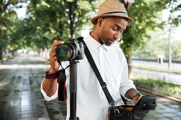 Junger mann im park mit hut, kamera haltend