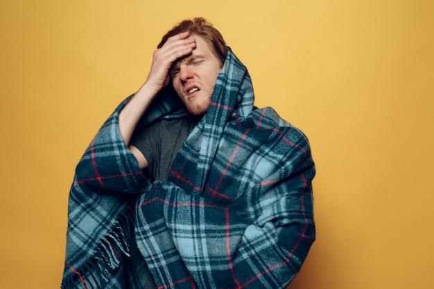 Junger mann im plaid husten mit kopfschmerzen eingewickelt
