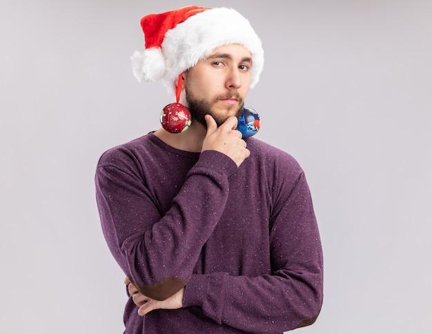 Junger mann im purpurroten pullover und in der weihnachtsmannmütze, die lustige brille mit weihnachtskugeln auf seinen ohren tragen, die kamera mit nachdenklichem ausdruck denkend über weißem hintergrund stehend betrachten