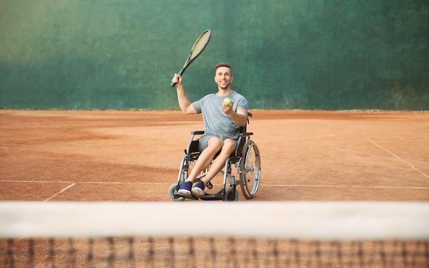 Junger mann im rollstuhl beim tennisspielen auf dem platz