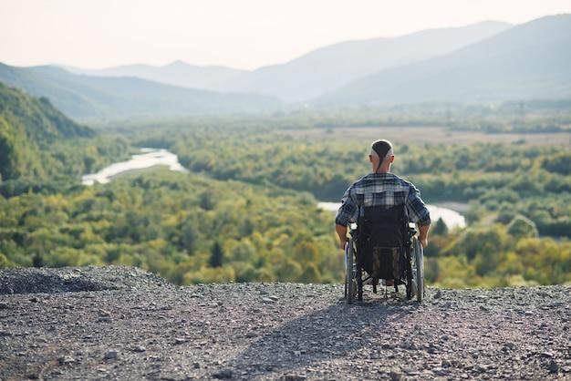 Junger mann im rollstuhl, der frische luft am sonnigen tag auf den bergen genießt