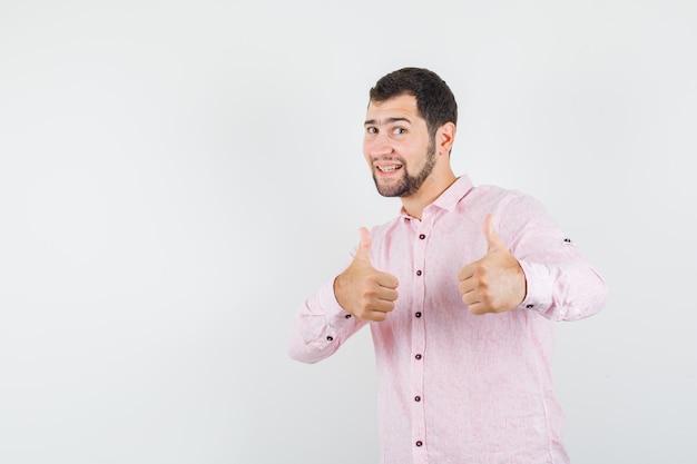 Junger mann im rosa hemd, das daumen oben zeigt und glücklich schaut