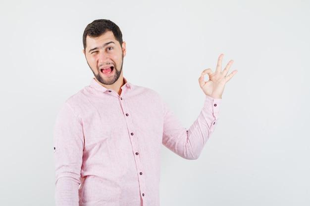 Junger mann im rosa hemd, das ok zeichen zeigt, auge zwinkert und verrückt aussieht