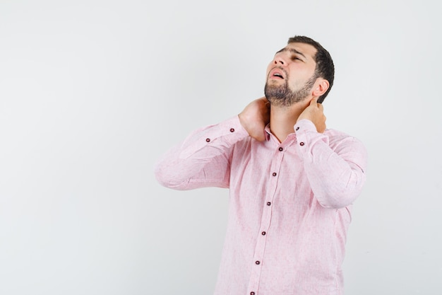 Junger mann im rosa hemd, das unter nackenschmerzen leidet und müde aussieht