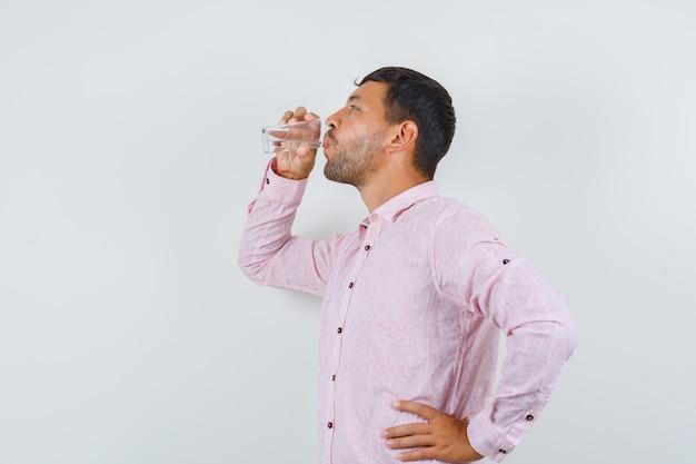 Junger mann im rosa hemd trinkt wasser und schaut durstig.