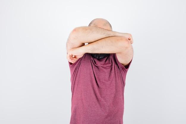 Junger mann im rosa t-shirt, das das gesicht mit den armen bedeckt und ernst aussieht, vorderansicht.