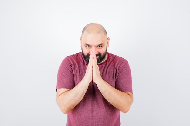 Junger mann im rosa t-shirt mit namaste-geste, vorderansicht.