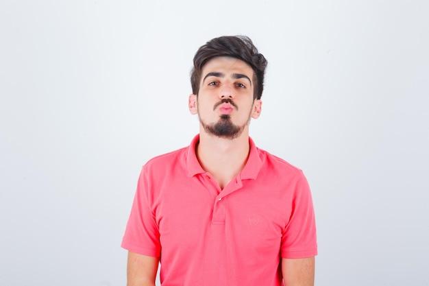 Junger mann im rosa t-shirt schmollende lippen und sieht elegant aus, vorderansicht.