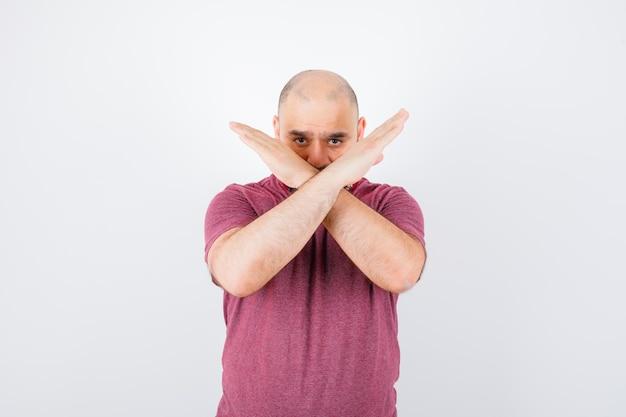Junger mann im rosafarbenen t-shirt, das einschränkung oder x-geste zeigt und ernst aussieht, vorderansicht.