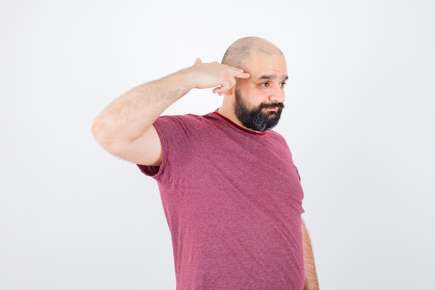 Junger mann im rosafarbenen t-shirt, das waffengeste zeigt und düster aussieht, vorderansicht.