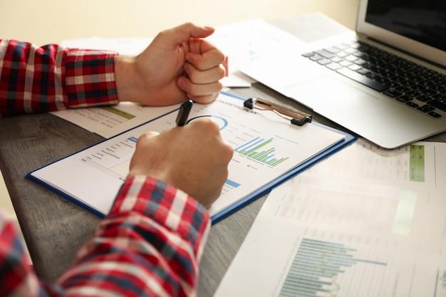 Junger mann im roten hemd beschäftigt sich mit finanzplanung