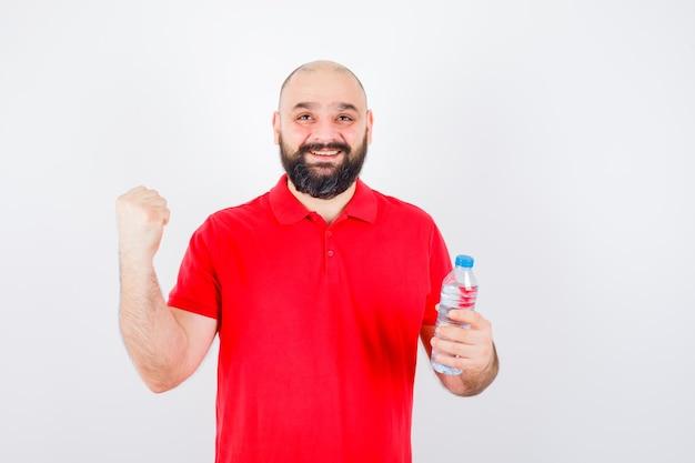 Junger mann im roten hemd, das flasche hält, während er erfolgsgeste zeigt und glücklich, vorderansicht schaut.