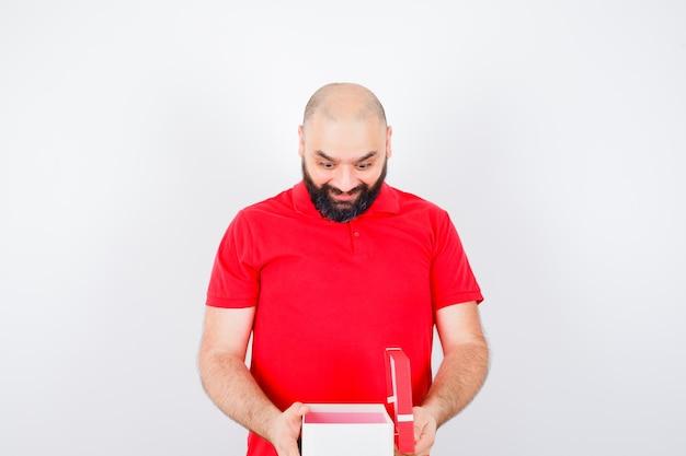 Junger mann im roten hemd, das geschenkbox öffnet und glücklich schaut, vorderansicht.