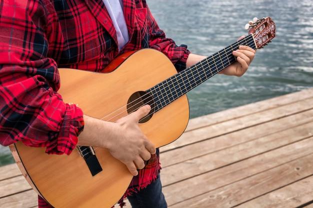 Junger mann im roten hemd spielt gitarre in der nähe eines sees in einem park