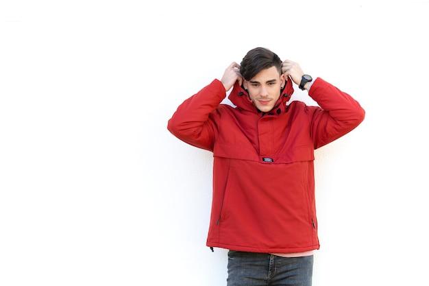 Junger mann im roten mantel über weißer wand