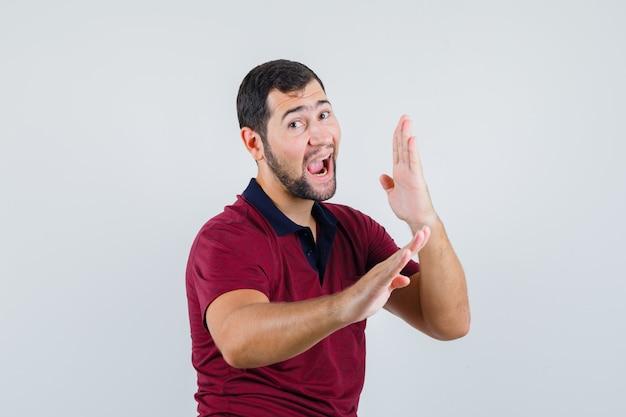 Junger mann im roten t-shirt hält hände in der vorbeugenden weise und schaut selbstbewusst, vorderansicht.