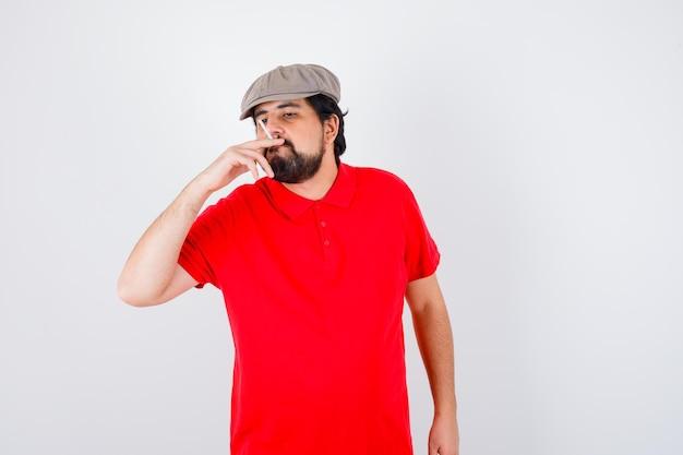 Junger mann im roten t-shirt, mützenrauchen, vorderansicht.