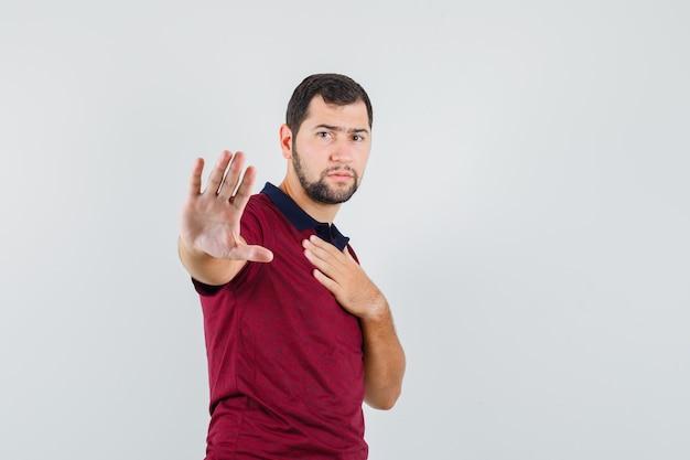Junger mann im roten t-shirt zeigt stoppgeste, während hand auf brust haltend und ernst, vorderansicht schauend.