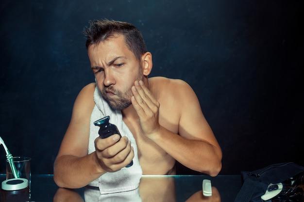 Junger mann im schlafzimmer sitzt vor dem spiegel und kratzt sich am bart