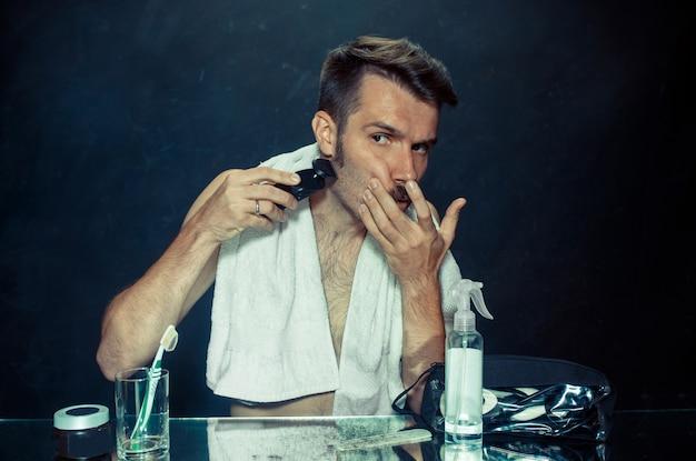 Junger mann im schlafzimmer sitzt vor dem spiegel und kratzt sich zu hause am bart