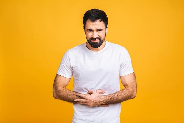 Junger mann im schmerz, der seinen verletzten magen lokalisiert auf dem gelben hintergrund hält. bauchschmerzen.