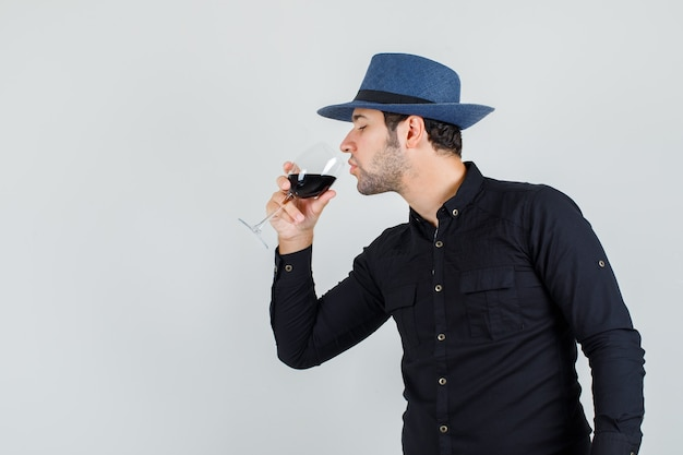 Junger mann im schwarzen hemd, hut, der alkohol trinkt