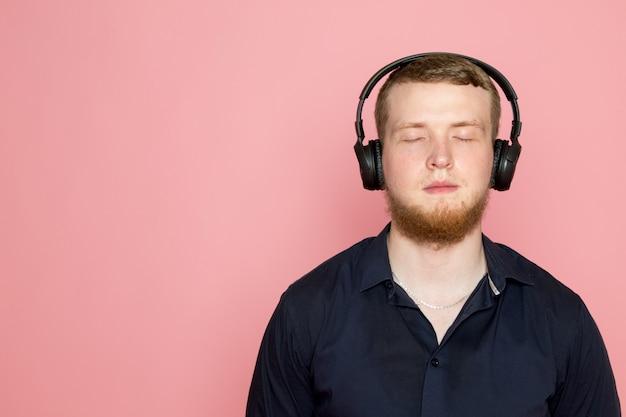 Junger mann im schwarzen hemd mit schwarzen kopfhörern