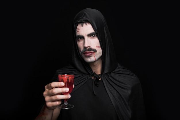 Junger mann im schwarzen kostüm, das im studio mit glas aufwirft
