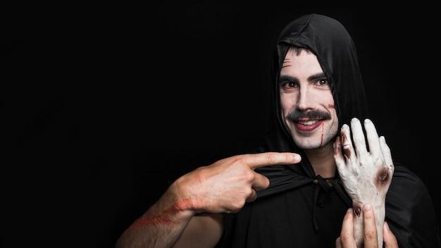 Junger mann im schwarzen mantel, der künstliche hand der leiche zeigt