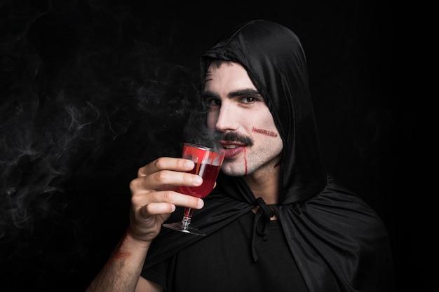 Junger mann im schwarzen mantel mit dem weißen gesicht, das dämpfende rote flüssigkeit trinkt