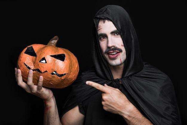 Junger mann im schwarzen mantel zeigend auf halloween-kürbis