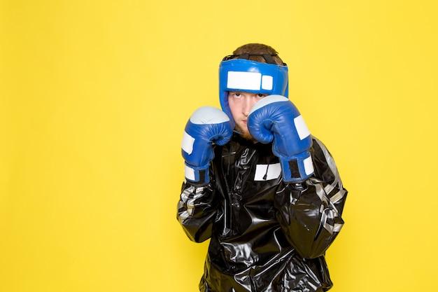 Junger mann im schwarzen sportanzug und in den blauen boxhandschuhen
