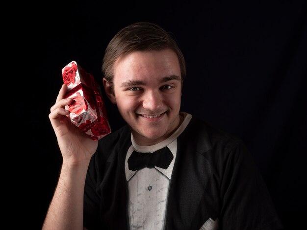 Junger mann im schwarzen t-shirt anzug schüttelt ein rotes geschenk mit überraschung auf einer schwarzen wand