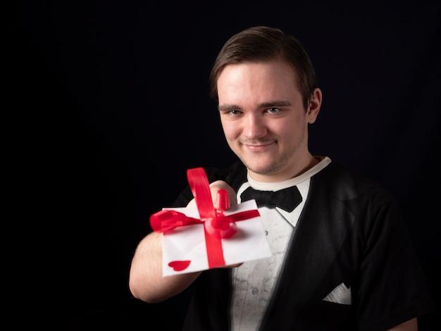 Junger mann im schwarzen t-shirt-anzug streckt seine hand mit einer weißen postkarte auf einem schwarzen aus
