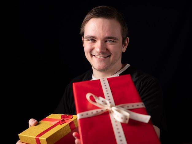 Junger mann im schwarzen t-shirt-anzug streckt seine hand mit geschenken auf einem schwarzen aus