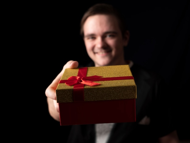 Junger mann im schwarzen t-shirt anzug streckt seine hand mit rotem und goldenem geschenk auf einem schwarzen aus