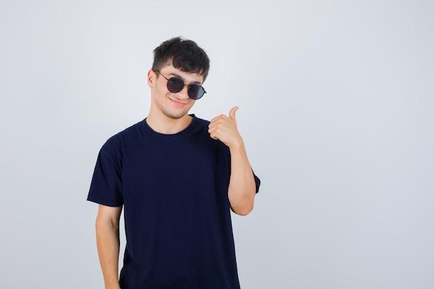 Junger mann im schwarzen t-shirt, das daumen oben zeigt und selbstbewusst, vorderansicht schaut.