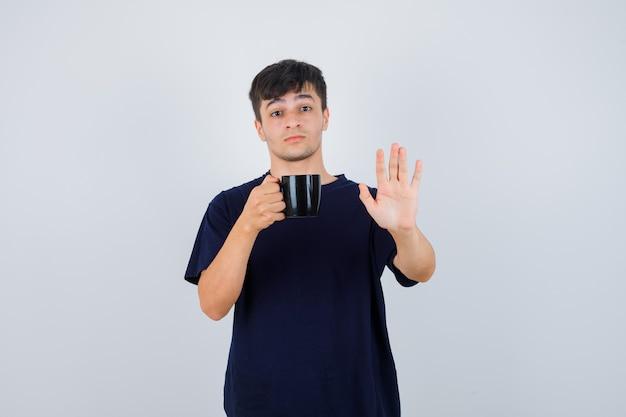 Junger mann im schwarzen t-shirt, das tasse tee hält, stoppgeste zeigt und ängstlich schaut, vorderansicht.