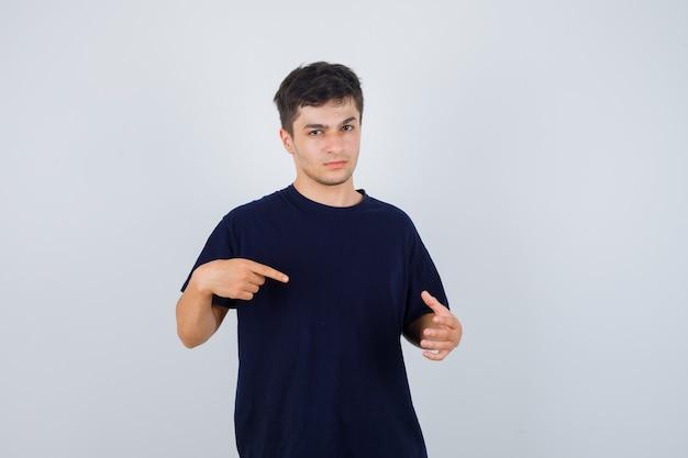 Junger mann im schwarzen t-shirt, der auf seine handfläche zeigt, breitete sich aus und sah ernst aus, vorderansicht.