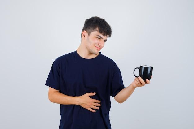 Junger mann im schwarzen t-shirt, der tasse betrachtet und nachdenklich, vorderansicht schaut.