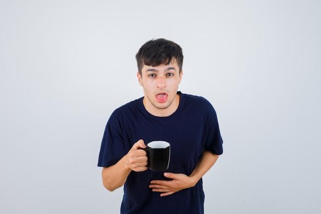 Junger mann im schwarzen t-shirt fühlt sich übel, während er tasse tee hält und unwohl schaut, vorderansicht.