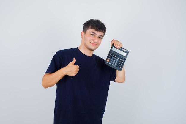 Junger mann im schwarzen t-shirt hält taschenrechner, zeigt daumen hoch und schaut erfreut, vorderansicht.