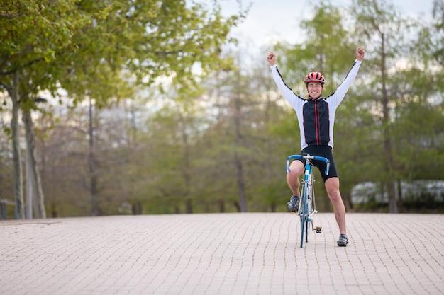 Junger mann im sturzhelm und in sportkleidung, die hände anheben und sieg beim fahren des fahrrades auf pflasterung im park feiern