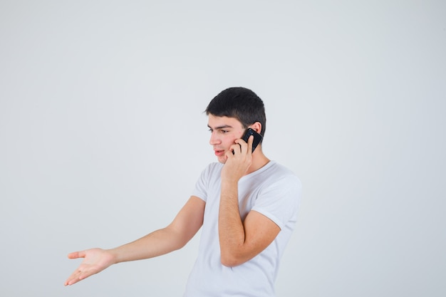 Junger mann im t-shirt, das auf handy spricht und aufgeregt, vorderansicht schaut.