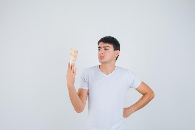 Junger mann im t-shirt, das eurobanknote hält, eurobanknote betrachtet und fokussierte vorderansicht schaut.