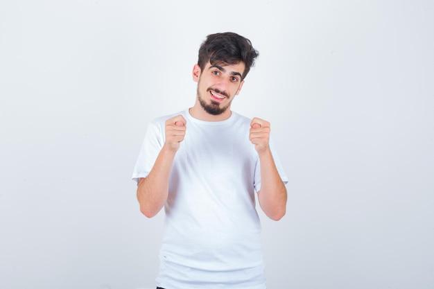 Junger mann im t-shirt, das feigenzeichen zeigt und lustig aussieht