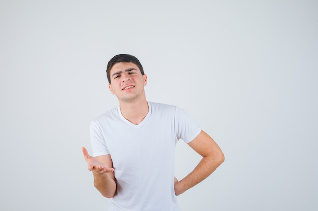 Junger mann im t-shirt, das hand in der fragenden geste streckt und selbstbewusst, vorderansicht schaut.