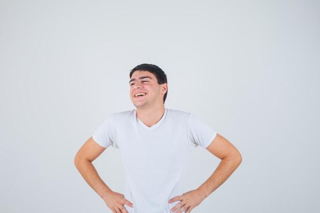Junger mann im t-shirt, das mit den händen auf der taille aufwirft und freudig, vorderansicht schaut.