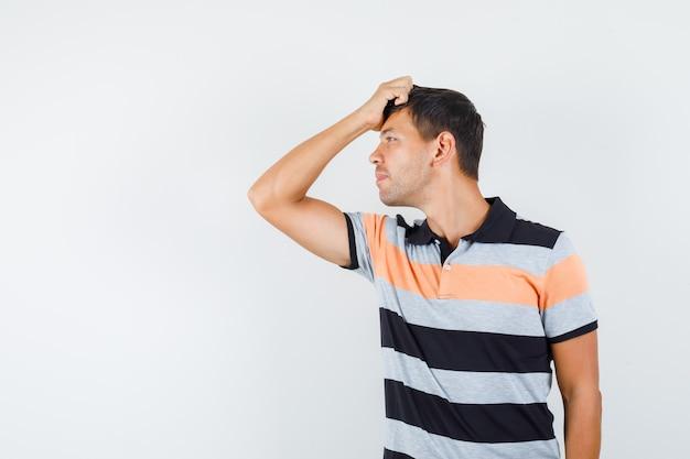 Junger mann im t-shirt, das mit hand auf haar aufwirft und gutaussehend schaut
