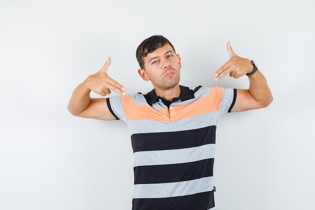 Junger mann im t-shirt, das mit waffengeste aufwirft und cool schaut